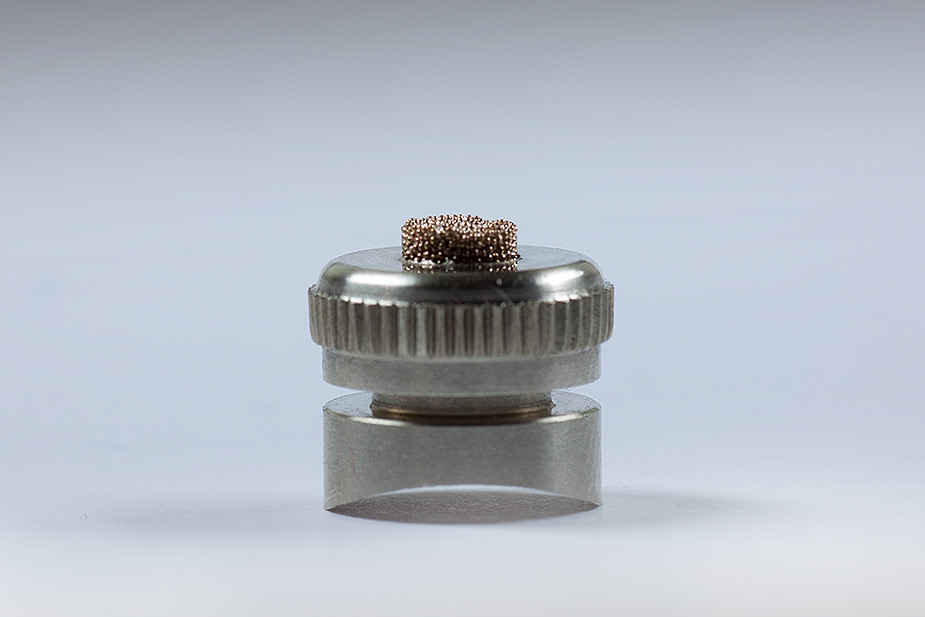 a nickel silver JoyKey showing the cap screwed onto the base and the WaterWick sinter filter showing through the middle of the cap in front of a pale blue background
