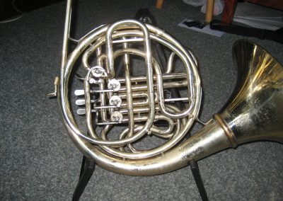 a silver Conn 8D standing upright with three JoyKey spit valves installed
