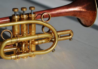 yellow brass cornet with a red brass bell and JoyKey spit valves installed on the main tuning slide and third valve slide