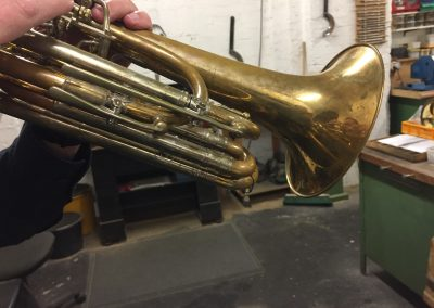 a bass trumpet being held in playing position to locate the positions for four JoyKey spit valves
