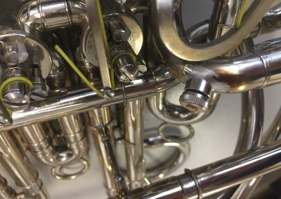 a JoyKey spit valve installed on the bend after the main tuning slide on a silver French horn