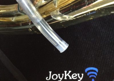 a ten centimeter long drop catcher tube half full of water drained from a JoyKey automatic water drainage spit valve on the lead pipe in front of a black lapcloth with the JoyKey logo on it
