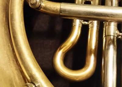 a close up of two JoyKey spit valves installed on a French horn