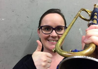 Sarah Slater smiling holding her baroque trumpet and giving a thumbs up next to the JoyKey spit valve on the second bend after the lead pipe