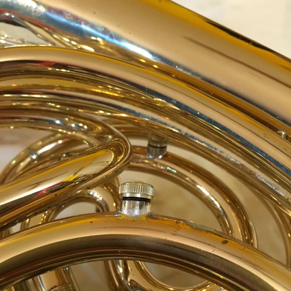 a close up of the JoyKey spit valve on the lead pipe and third valve slide of a double horn