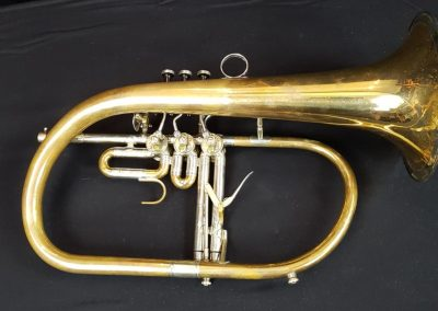 a rotary valved flugelhorn lying on its side fitted with two JoyKey spit valves