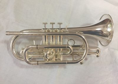 a silver cornet lying on its side fitted with two JoyKey spit valves one on the main tuning slide and one on the third valve slide